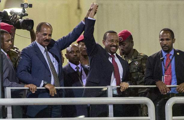 FILE - In this Sunday July 15, 2018 file photo, Eritrean President Isaias Afwerki, second left, and Ethiopia's Prime Minister Abiy Ahmed, center, hold hands as they wave at the crowds in Addis Ababa, Ethiopia. Once official rivals, the leaders of Ethiopia and Eritrea have embraced warmly to the roar of a crowd of thousands at a concert celebrating the end of a long state of war. The 2019 Nobel Peace Prize was given to Ethiopian Prime Minister Abiy Ahmed on Friday Oct. 11, 2019. (AP Photo/Mulugeta Ayene, File)