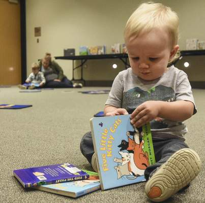 Michelle Davies | The Journal Gazette Theo Weckenbrock, 1, of Fort Wayne  prepares to check out the reading selection during Friday morning's Storytime session at the downtown Allen County Public Library.