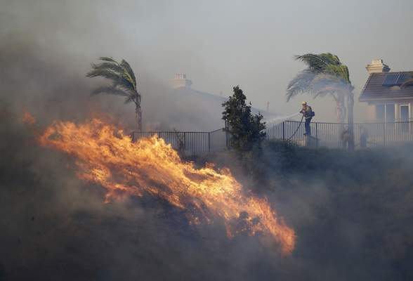 Associated Press A firefighter sprays water in front of an advancing wildfire Friday in Porter Ranch, Calif.