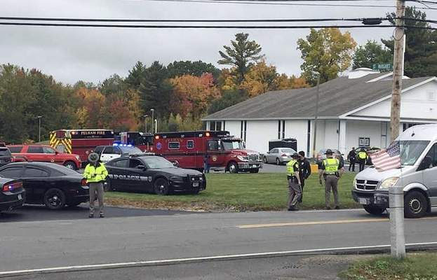 In this photo provided by WMUR-TV, police stand outside the New England Pentecostal Church on Saturday, Oct. 12, 2019, in Pelham, N.H. (Siobhan Lopez/WMUR-TV via AP)