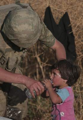 Associated Press: This June 14, 2015, file photo shows a Turkish soldier offering water to a Syrian refugee child after crossing into Turkey from Syria, in Akcakale, Sanliurfa province, southeast Turkey. The photo was widely shared on Twitter this week, suggesting the recent assault in northern Syria has not hurt civilians.