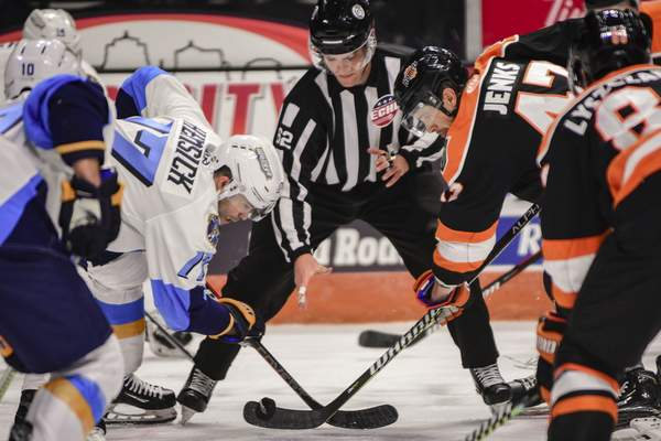 Mike Moore | The Journal Gazette Komets forward A.J. Jenks and Toledo forward T.J. Hensick faceoff in the first period at Memorial Coliseum on Saturday.