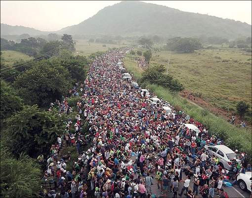 Associated Press Members of a migrant caravan bound for the southern U.S. border crowd a road after federal police briefly blocked their way outside the Mexican town of Arriaga on Oct. 27, 2018.