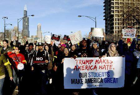 Associated Press: In this Friday, March 11, 2016, file photo, protestors march in Chicago before a rally for Republican presidential candidate Donald Trump at the University of Illinois-Chicago. On Friday, the Associated Press reported on a manipulated version of this photo circulating online with the foreground sign's slogan changed.