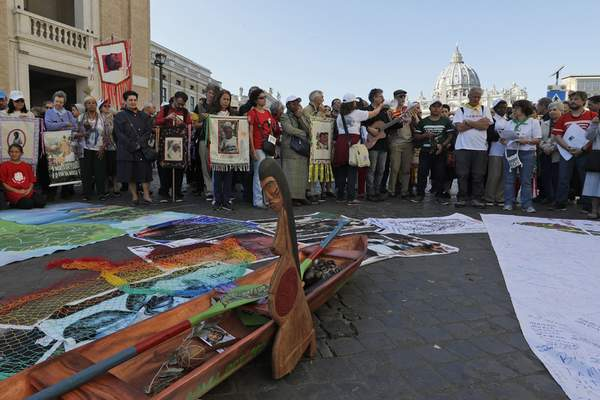 In this photo taken on Saturday, Oct. 19, 2019, members of Amazon indigenous populations prepare for a a Via Crucis (Way of the Cross) procession from St. Angelo Castle to the Vatican.  (AP Photo/Andrew Medichini)