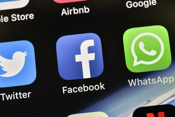 FILE - In this Nov. 15, 2018, file photo the icons of Facebook and WhatsApp are pictured on an iPhone in Gelsenkirchen, Germany. (AP Photo/Martin Meissner, File)