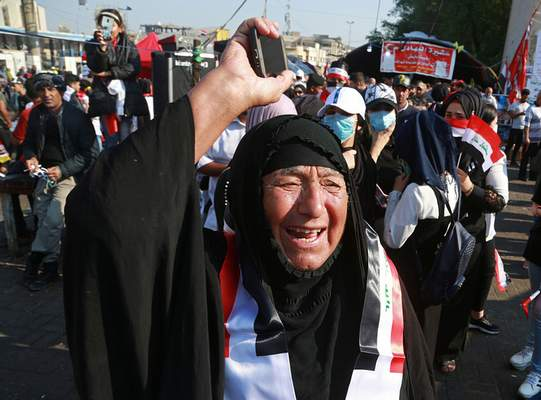 Associated Press  Anti-government protesters demonstrate Thursday  in Baghdad. Iraq's president said he would approve early elections, a win for the protesters.