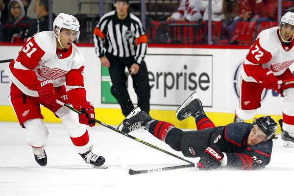 Karl B DeBlaker | Associated Press Carolina Hurricanes' Erik Haula (56) dives to the ice for the puck in front of Detroit Red Wings' Valtteri Filppula (51) during the first period of an NHL hockey game in Raleigh, N.C., Friday.