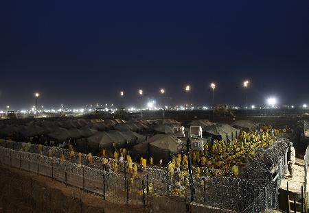 Associated Press: In this March 16, 2009, file photo, detainees walk after a prayer at a U.S. military detention facility, Camp Bucca, Iraq. On Friday, the Associated Press reported on stories circulating online incorrectly asserting that President Barack Obama, who served two terms from 2009 to 2017, freed Abu Bakr al-Baghdadi, Islamic State group leader, from the prison during his presidency.