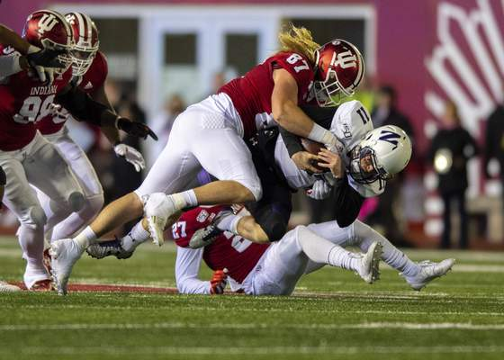 Northwestern quarterback Aidan Smith (11) is hit by Indiana defensive lineman Michael Ziemba (87) while rushing the ball for a first down during the first half of an NCAA college football game, Saturday, Nov. 2, 2019, in Bloomington, Ind. (AP Photo/Doug McSchooler)