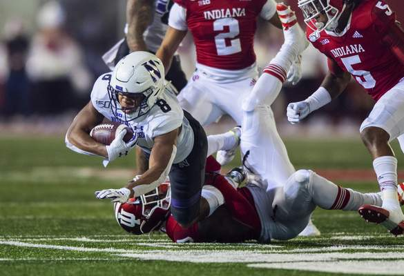 Northwestern wide receiver Kyric McGowan (8) is tripped up by an Indiana defender during the first half of an NCAA college football game, Saturday, Nov. 2, 2019, in Bloomington, Ind. (AP Photo/Doug McSchooler)