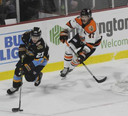 Justin A. Cohn | Journal Gazette Komets forward A.J. Jenks chases the  Walleye's Brandon Anselmini for the puck Sunday at the Huntington Center in Toledo.