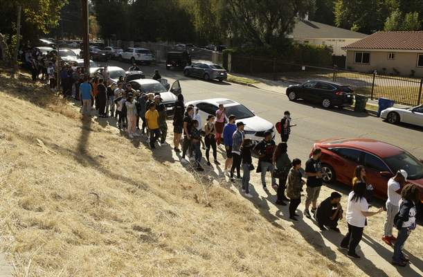 People line up around the block of singer Chris Brown's home in the Tarzana area of Los Angeles Wednesday, Nov. 6, 2019. (AP Photo/Damian Dovarganes)