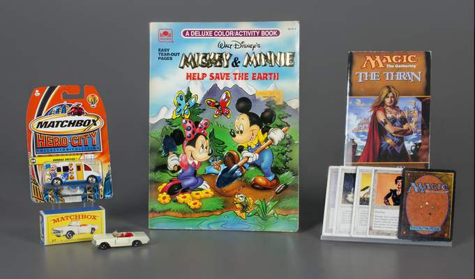 In this Oct. 7, 2019 photo provided by the National Toy Hall of Fame, Matchbox Cars, left, the coloring book, center, and the collectible card game Magic: The Gathering were inducted into the National Toy Hall of Fame in Rochester, N.Y. (Victoria Gray/The Strong, National Toy Hall of Fame via AP)
