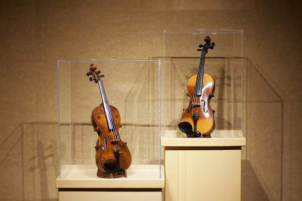 "The Zimmerman Violin, left, and the Berlin Gypsy Violin are two of the violins on display during the ""Strings of the Holocaust"" exhibition in the Weatherhead Gallery at the University of Saint Francis through Dec. 1. (Photos by Katie Fyfe 