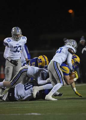 Katie Fyfe | The Journal Gazette Homestead senior Jake Archbold gets tackled during the first quarter against Carroll at Homestead High School on Friday.