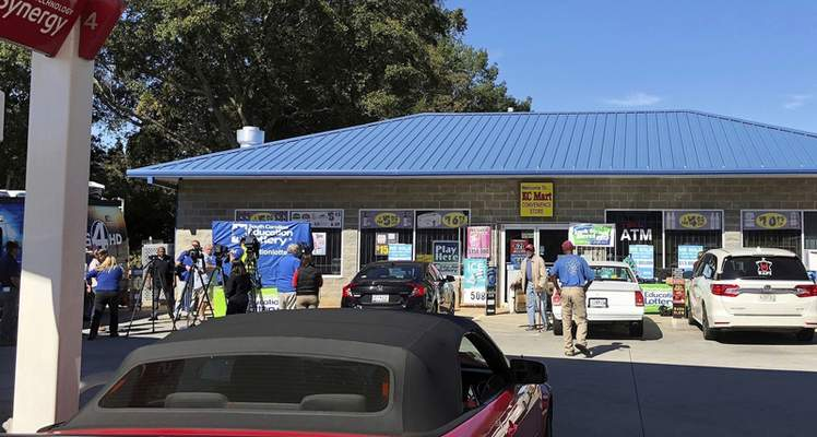 FILE - In this Oct. 24, 2018, file photo, media, at left, record people entering the KC Mart in Simpsonville, S.C., after it was announced the winning Mega Millions lottery ticket was purchased at the store. South Carolina revenue officials say they have started mailing $50 rebate checks to eligible taxpayers. The first 400,000 checks were sent out this week and all 1.2 million checks should be in the mail by Dec. 2, 2019. Lawmakers backed Gov. Henry McMaster's call to use for the rebates the $61 million of state income tax paid by South Carolina's unidentified winner of the October 2018 $878 million Mega Million lottery prize. Married couples will have to share one $50 check. (AP Photo/Jeffrey Collins, File)