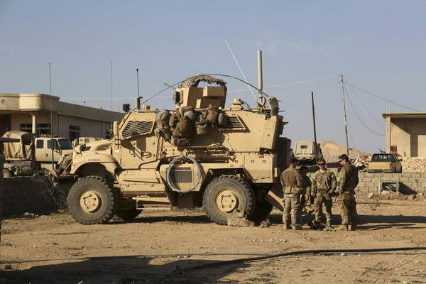 FILE - In this Feb. 23, 2017 photo, U.S. Army soldiers stand outside their armored vehicle on a joint base with Iraqi army south of Mosul, Iraq. Iraqi security officials say 17 Katyusha rockets have hit an Iraqi air base south of the city of Mosul that houses American troops. The two officials say there are no immediate reports of casualties from the attack, which occurred on Friday, Nov. 8, 2019. (AP Photo/ Khalid Mohammed, File)