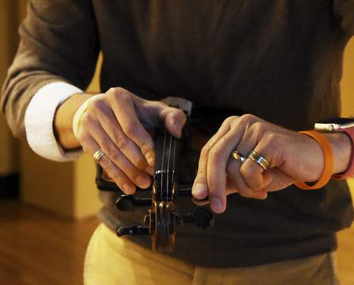 Miles Fulwider, chair of the music department at University of Saint Francis, tunes the Bielski Violin. This violin was played by a klezmer musician and the restoration of this violin is dedicated to the Bielski partisans who fought and saved 1,230 Jews during war.