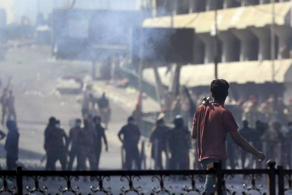 Iraqi riot police fire tear gas to disperse anti-government protesters gathering on bridge in central Baghdad, Iraq, Saturday, Nov. 9, 2019. (AP Photo/Hadi Mizban)