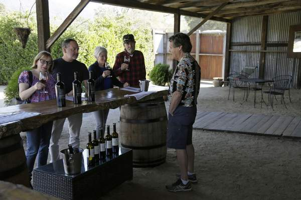 In this Wednesday, Nov. 6, 2019 photo, Mark Dankowski, right, leads a tasting for a group of people visiting the Soda Rock Winery in Healdsburg, Calif. (AP Photo/Eric Risberg)