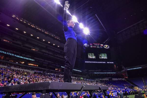 Mike Moore | The Journal Gazette A Drum Major with the Homestead High School Marching Band directs her bandmates during the ISSMA State Marching Band Finals at Lucas Oil Stadium in Indianapolis on Saturday.