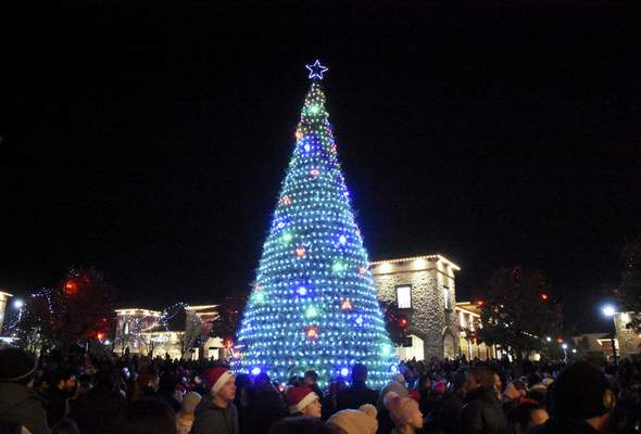 The 48-foot tree casts its glow over the crowd Saturday. Light and music shows run nightly.