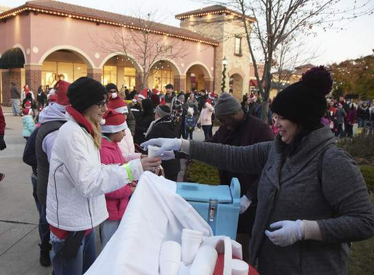 Photos by Katie Fyfe | The Journal Gazette Long lines form for hot chocolate Saturday during a Christmas tree lighting celebration that drew 3,000 to 4,000 to the Jefferson Pointe shopping center.