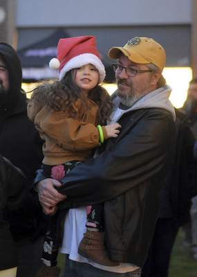 Katie Fyfe | The Journal Gazette Emerson Helmke, 3, waits in the hot chocolate line with her Grandpa Charles during the Jefferson Pointe Christmas Tree Lighting Celebration at Jefferson Pointe on Saturday, November 9th, 2019.