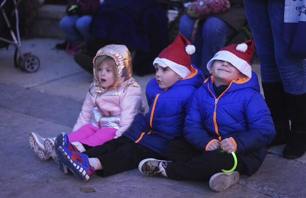 Katie Fyfe | The Journal Gazette Addi Moschel, 5, Lane Holiday, 4, and Hungter Holiday, 3, (left to right) wait for the tree to light up during the Jefferson Pointe Christmas Tree Lighting Celebration at Jefferson Pointe on Saturday, November 9th, 2019.