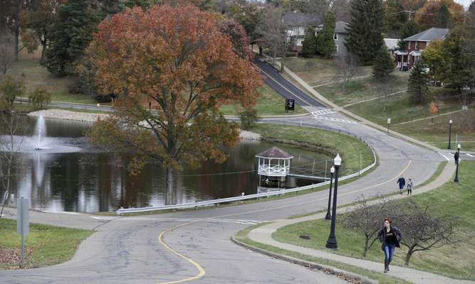 In this Monday, Nov. 4, 2019, photo, students walk by the the Muskingum University's lake, in New Concord, Ohio. (AP Photo/Tony Dejak)