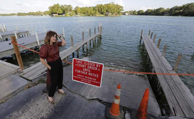 Tess Coody-Anders, a university executive and homeowner near Lake McQueeney, one of the dams slated to be drained, stands near a sign showing the lake is closed, Sept. 30, 2019, in Lake McQueeney, Texas. (AP Photo/Eric Gay)