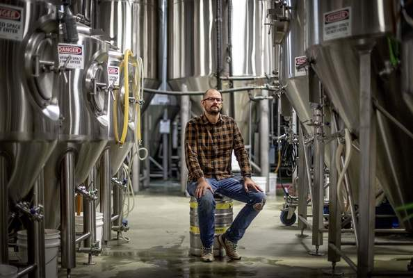 Joel Iverson, chief operating officer of Monday Night Brewing, is photographed in the brewery that sits beside Reservoir No. 1, a 180 million-gallon water supply that has been out of service much of the past few decades, Oct. 15, 2019, in Atlanta. (AP Photo/David Goldman)