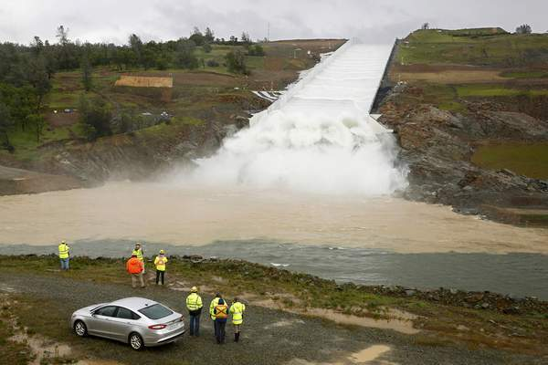 FILE - In this April 2, 2019, file photo, water flows down the Oroville Dam spillway in Oroville, Calif. The state spent $1.1 billion repairing the Lake Oroville spillway, enacted new emergency plan requirements and launched a review of 93 other dams with similar spillways. (AP Photo/Rich Pedroncelli, File)