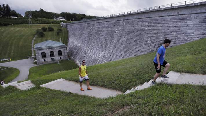 In this July 25, 2018, photograph, men climb stairs while working out at the Wachusett Reservoir Dam in Clinton, Mass. The dam, which holds up to 65 billion gallons of water, is considered high hazard because of its destructive potential should it fail but also is rated as in satisfactory condition. (AP Photo/Charles Krupa)