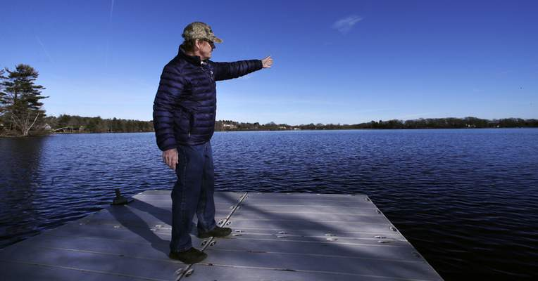 In this Dec. 27, 2018, photo, Murray Beach, an investment banker who lives on the shore of Willett Pond, points out the spillway of the lake, which is located on the border of Norwood and Walpole, Mass. (AP Photo/Charles Krupa)
