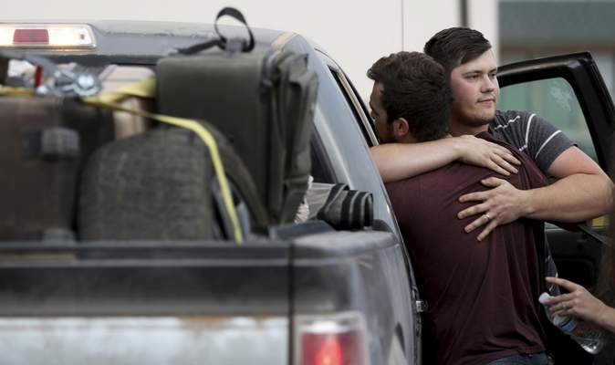 Cole Langford, left, and Hayden Spenct, of the Mormon colony in La Mora, Mexico, hug during a rendezvous in a gas station in Douglas, Ariz., Saturday, Nov. 9, 2019.  (Kelly Presnell/Arizona Daily Star via AP)