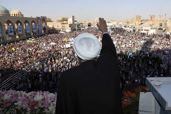 In this photo released by the official website of the office of the Iranian Presidency, President Hassan Rouhani waves to the crowd in a public gathering at the city of Yazd, some 410 miles (680 kilometers) southeast of the capital Tehran, Iran, Sunday, Nov. 10, 2019. (Office of the Iranian Presidency via AP)