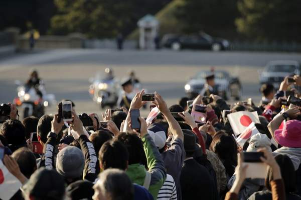 Spectators take pictures as the royal motorcade of Japanese Emperor Naruhito and Empress Masako approaches them in Tokyo, Sunday, Nov. 10, 2019. (AP Photo/Jae C. Hong)