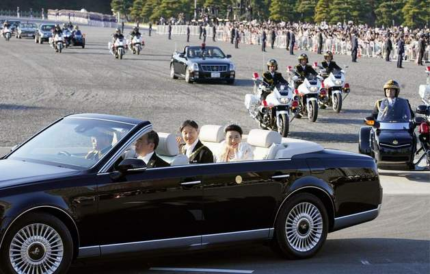 Japanese Emperor Naruhito, center left, and Empress Masako, center right, wave to spectators during the royal motorcade in Tokyo, Sunday, Nov. 10, 2019.(Shigeyuki Inakumao/Kyodo News via AP)