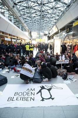 Climate activists block the entrance hall of the Tegel airport in Berlin, Germany, Sunday, Nov. 10, 2019. A banner reads 'stay on the ground'. (Fabian Sommer/dpa via AP)