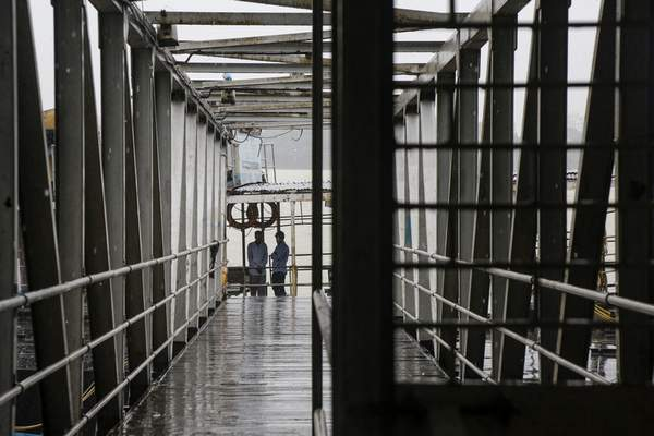 Security officers stand on an empty jetty leading to a ferry service, suspended due to cyclonic storm, on the Hooghly River in Kolkata, India, Saturday, Nov. 9, 2019. (AP Photo/Bikas Das)