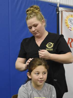 Rachel Von Stroup   The Journal Gazette Amira Barker, 9, gets her hair straightened by Tiffany Kuhn at the Ravenscroft Beauty College booth during the Girls World Expo at Turnstone Center For Children and Adults with Disabilities in Fort Wayne, IN on Sunday November 10, 2019.