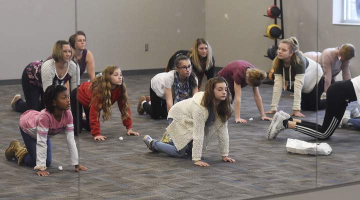 Rachel Von Stroup   The Journal Gazette Girls stretch during the Mindful Meditation, Breathing, Yoga Basics class led by Amanda Horsewood during the Girls World Expo at Turnstone Center For Children and Adults with Disabilities in Fort Wayne, IN on Sunday November 10, 2019.