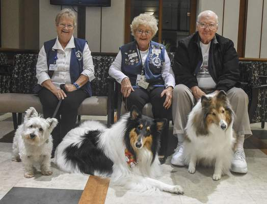 Michelle Davies | The Journal Gazette Members of the Three Rivers Visiting Dogs, from left, Jill Kennedy, with Wiley, 5, Sharon Laupp, with Patches, 6, and Tom Laupp, with Francis, 3, sit in the lobby of St. Joseph Hospital.