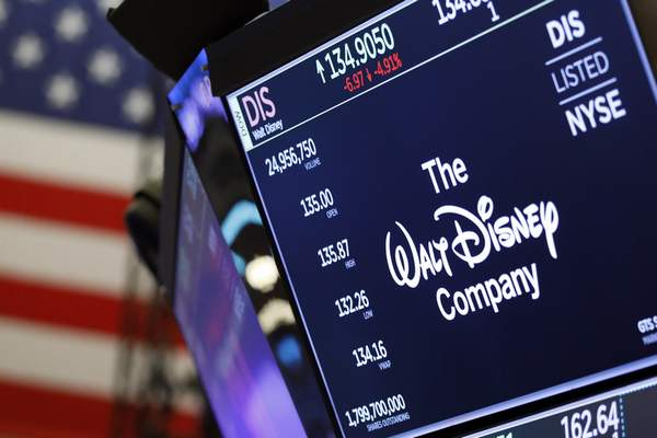 FILE - In this Aug. 7, 2019, file photo the logo for The Walt Disney Company appears above a trading post on the floor of the New York Stock Exchange. On Tuesday, Nov. 12, Disney Plus launches its streaming service. (AP Photo/Richard Drew, File)