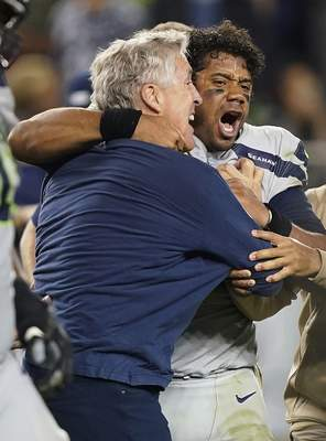 Associated Press Seahawks head coach Pete Carroll, left, celebrates with quarterback Russell Wilson after the team beat the 49ers 27-24 in overtime Monday.