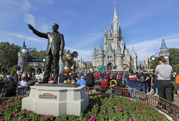 FILE - In this Jan. 9, 2019, file photo, guests watch a show near a statue of Walt Disney and Micky Mouse in front of the Cinderella Castle at the Magic Kingdom at Walt Disney World in Lake Buena Vista, Fla. Disney Plus says it hit more than 10 million sign-ups on its first day of launch, far exceeding expectations. Disney's mix of Marvel and Star Wars movies and shows, classic animated films and new series appears to be a hit out of the gate after its launch on Tuesday, Nov. 12. (AP Photo/John Raoux, File)