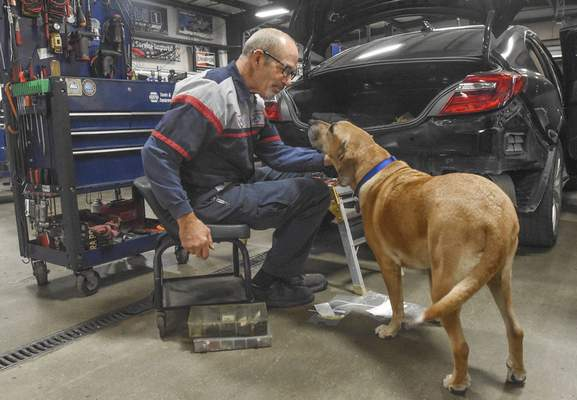 Michelle Davies | The Journal Gazette Charlie spends time with his owner, Rich Elzey, at Rich's Auto Center.