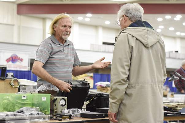 Rachel Von Stroup | The Journal Gazette Lee Rhoden, left, talks to a customer about a ham radio transceiver Sunday during the 47th annual Fort Wayne Hamfest & Computer Expo at Memorial Coliseum.